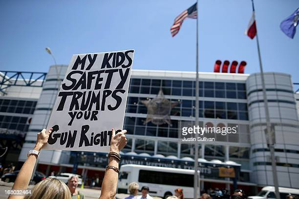 A protestor holds a sign during a demonstration in favor of gun regulation outside of the 2013 NRA Annual Meeting and Exhibits at the George R Brown...