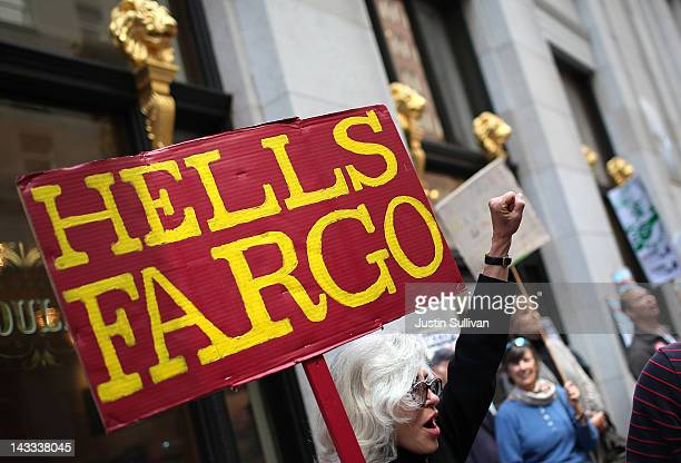 A protestor holds a sign during a demonstration outside of the Wells Fargo shareholders meeting on April 24 2012 in San Francisco California Hundreds...