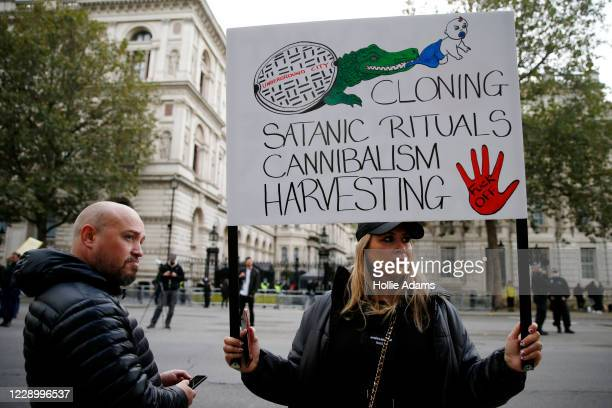 "Protestor holds a sign during a ""Save our Children"" rally outside Downing Street on October 10, 2020 in London, England. During the demonstration,..."