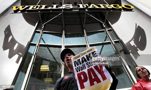 A protestor holds a sign in front of the Wells Fargo headquarters during a demonstration outside of the Wells Fargo Bank shareholders meeting April...