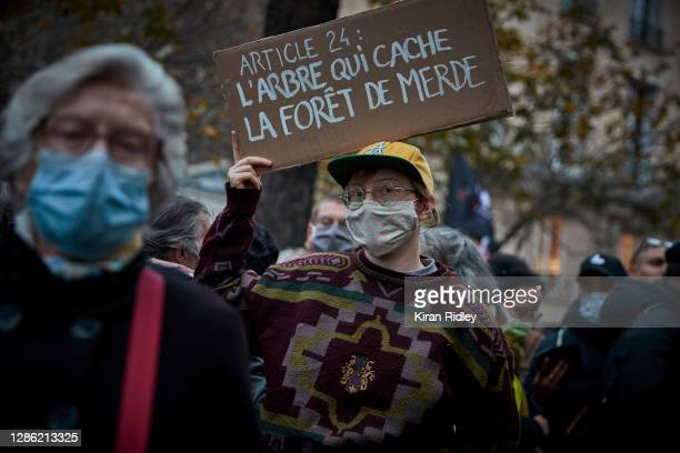 Protestor holds a sign readinProtestors demonstrate outside the National Assembly in protest to the French Government's proposed global security law...