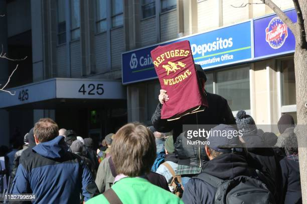 Protestor holds a sign saying 'refugees welcome' during a ProMuslim and AntiMuslim rally held in Toronto Ontario Canada on March 23 2019 Counter...