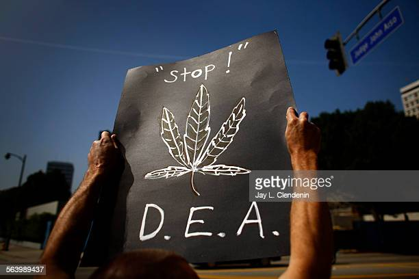 A protestor holds a sign that says 'Stop' along with a drawn marijuana leaf and the initials 'DEA' Supporters of medical marijuana use and...