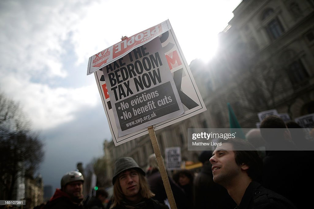 A protestor holds a sign while demonstrating against the proposed 'bedroom tax' gather in Trafalgar Square before marching to Downing Street on March 30, 2013 in London, England. Welfare groups are protesting the government's plans to cut benefits where families have surpassed the number of rooms they require.