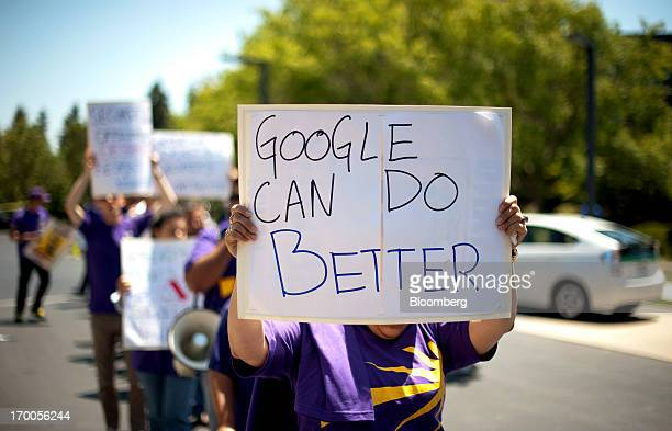 A protestor holds a sign while demonstrating outside at Google Inc's headquarters during the company's annual shareholders meeting in Mountain View...