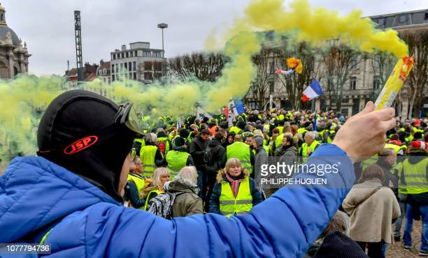 A protestor holds a yellow flare during a yellow vest antigovernment demonstration in Lille northern France on January 5 2019 The yellow vest...