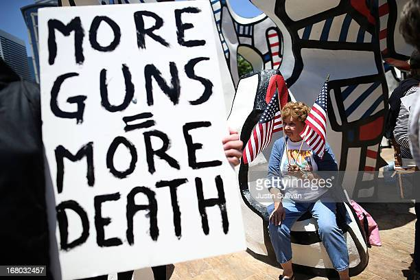 Protestor holds American flags during a demonstration in favor of gun regulation outside of the 2013 NRA Annual Meeting and Exhibits at the George R....