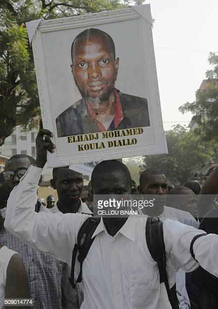 A protestor holds on February 8 2016 in Conakry a portrait of El Hadj Mohamed Diallo a journalist shot in clashes outside the offices of an...