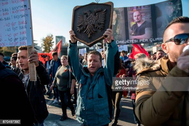A protestor holds the silhouetted black doubleheaded eagle symbol of Albania as Macedonian Albanians gather in Skopje on November 5 to protest...