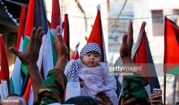 TOPSHOT A protestor holds up a baby in between Palestinian flags during a demonstration against US President Donald Trump's decision to recognise...