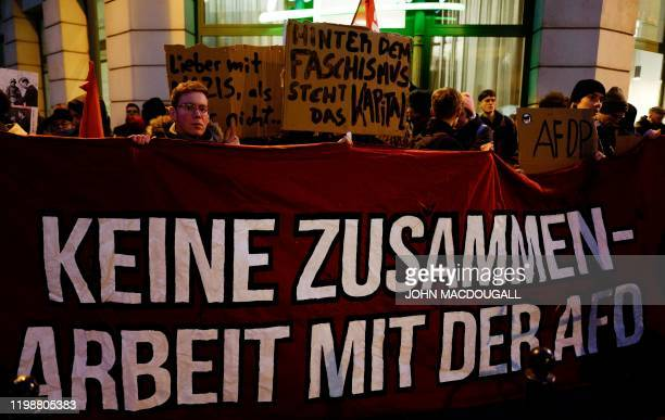 A protestor holds up a banner which reads No cooperation with the AFD during a rally outside the headquaters of the Free Democratic Party in Berlin...