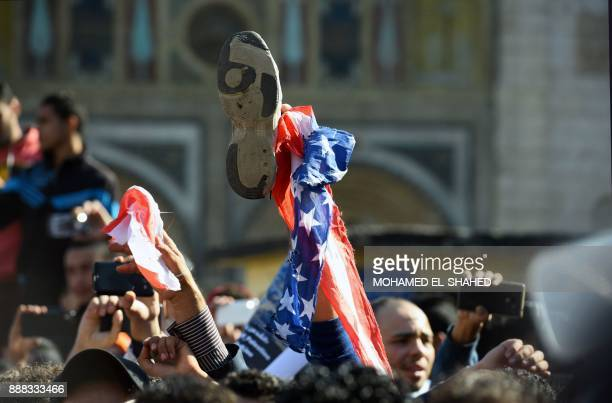 A protestor holds up a shoe next to an American flag as a sign of disrespect during a demonstration against US President Donald Trump's decision to...
