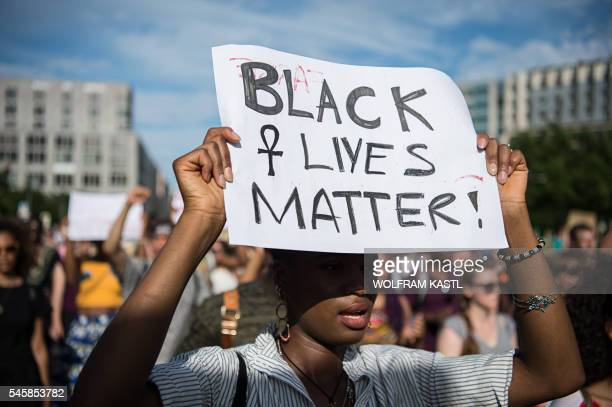 A protestor holds up a sign reading Black Lives Matter during a demonstration in Berlin on July 10 2016 with the motto Black Lives Matter No Justice...