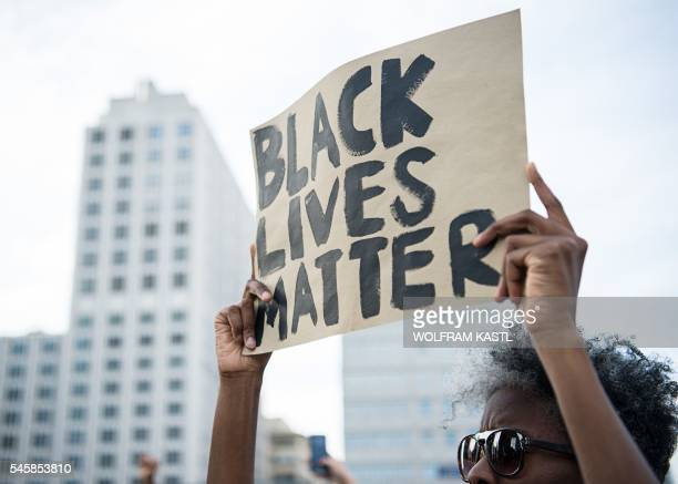 A protestor holds up a sign reading 'Black Lives Matter' during a demonstration in Berlin on July 10 2016 with the motto 'Black Lives Matter No...