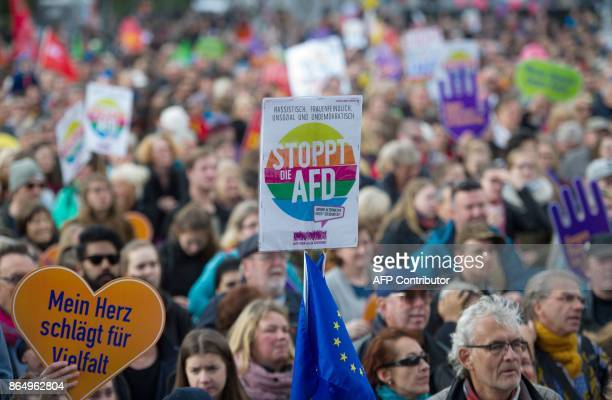 A protestor holds up a sign reading Stop the AFD during a demonstration against hate and racism in the Bundestag lower house of parliament to protest...