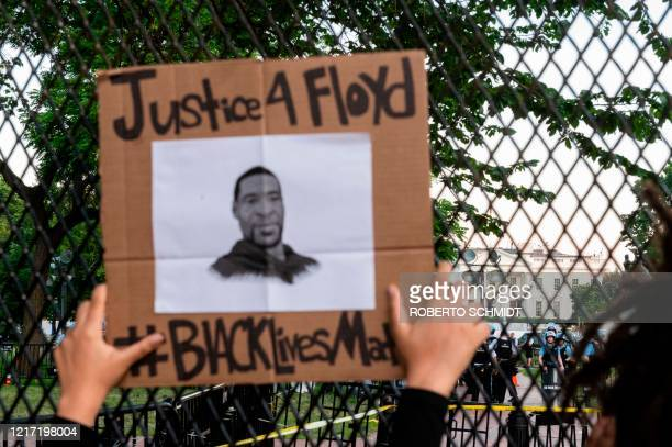 A protestor holds up a sign showing an image of slained resident of Minneapolis George Floyd against a metal fence recently erected in front of the...