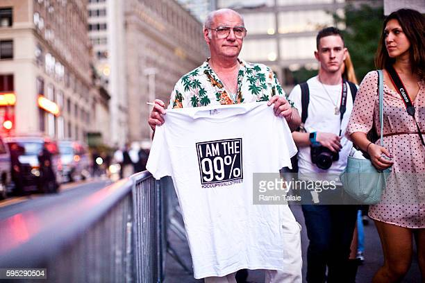 A protestor holds up a tshirt that reads 'I am the 99 percent' stands at Zuccotti Park during a demonstration in New York City on Saturday October 8...