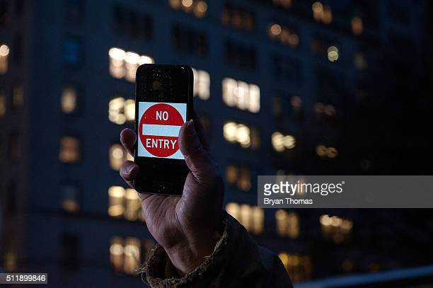 A protestor holds up an iPhone that reads 'No Entry' outside of the the Apple store on 5th Avenue on February 23 2016 in New York City Protestors...