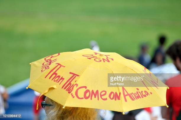 Protestor holds up an umbrella that readsquot We Are Better Than This Come on America ahead of an Abolish ICE protest to demand the halt of...