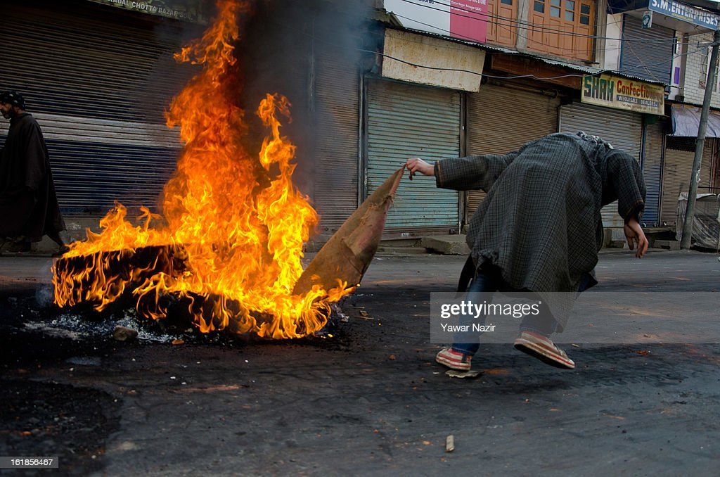 A protestor ignites tires during a strike call given by separatists against the execution of alleged Indian parliament attacker Mohammad Afzal Guru on February 17, 2013 in Srinagar, the summer capital of Indian Administered Kashmir, India. Normal life remains affected in Indian-administered Kashmir for the ninth consecutive day as a complete shutdown was observed on the call of separatist leader Syed Ali Shah Geelani. Afzal Guru was hanged on February 9 for his alleged role in the 2001 Indian parliament attack which left 14 dead. Clashes between Kashmiri youth and Indian police were also reported in several parts of the disputed Himalayan region, which was put under a strict curfew for a week by Indian authorities worried about massive public protests following Guru's hanging last Saturday.