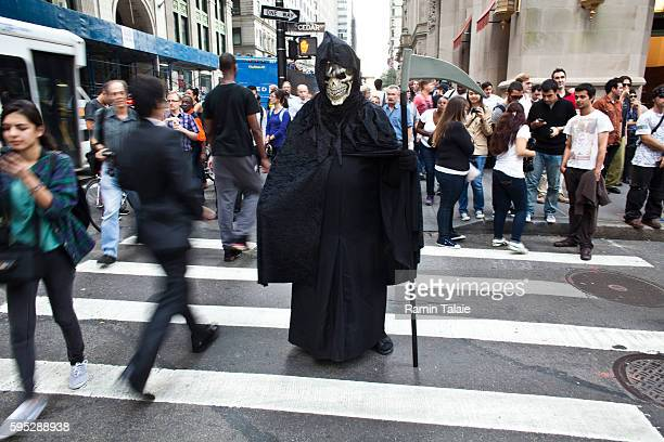 A protestor in a grim reaper costume crosses a street near Zuccotti Park where hundreds of demonstrators have camped out in Lower Manhattan for 14...