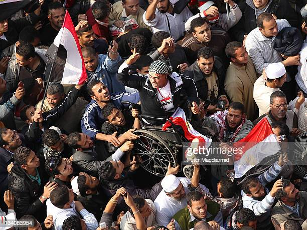 A protestor in a wheelchair is held aloft during a mass rally in Tahrir Square on November 25 2011 in Cairo Egypt Thousands of Egyptians are...