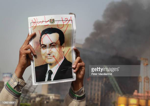A protestor in Tahrir Square holds a photo showing President Mubarak's face crossed out on January 29 2011 in Cairo Egypt Tens of thousands of...