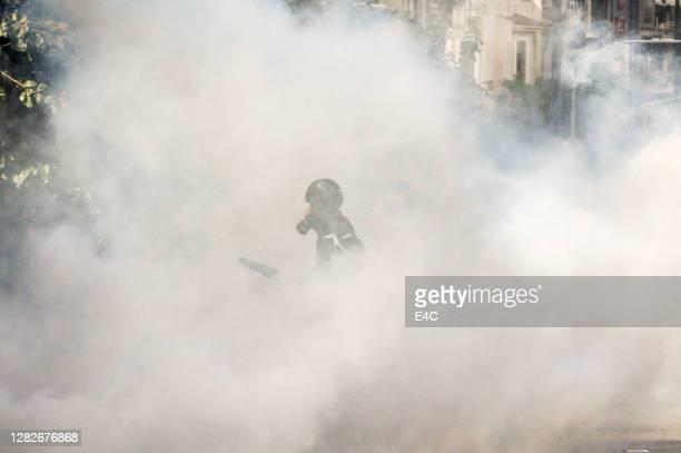 manifestante en nube de gas lacrimógeno - tear gas fotografías e imágenes de stock