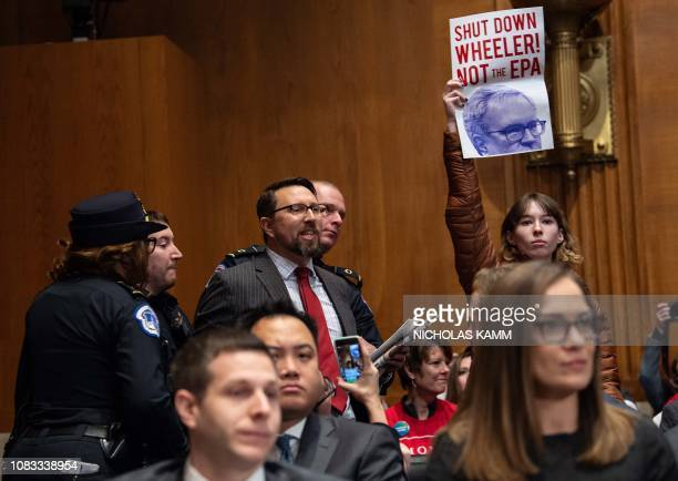 A protestor is arrested as another holds a sign during the confirmation hearing of Andrew Wheeler nominee to be Environmental Protection Agency...