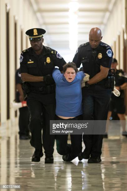 A protestor is arrested by Capitol Police officers outside the office of Sen Pat Toomey's while lobbying against the Senate GOP health care bill on...