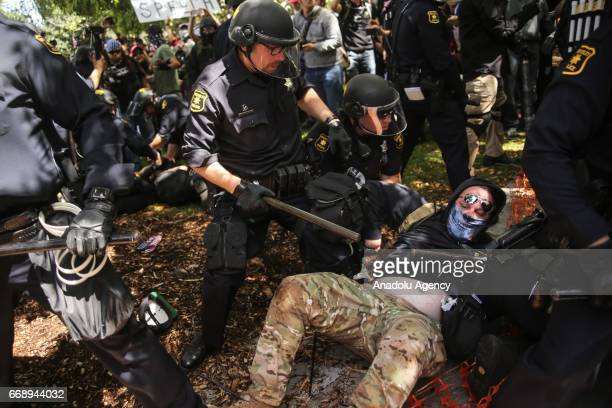 A protestor is arrested by police officers during a proTrump rally in Berkeley USA on April 15 2017 A large number of fights have occurred and people...