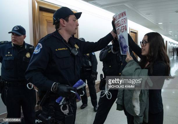 A protestor is arrested outside the confirmation hearing of Andrew Wheeler nominee to be Environmental Protection Agency administrator on Capitol...
