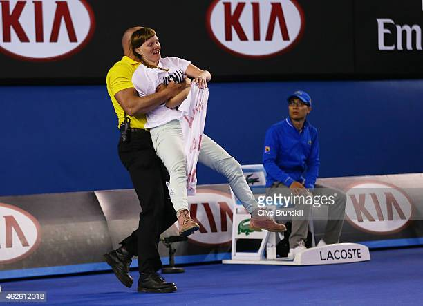 A protestor is carried from centre court at Rod Laver Arena during day 14 of the 2015 Australian Open at Melbourne Park on February 1 2015 in...