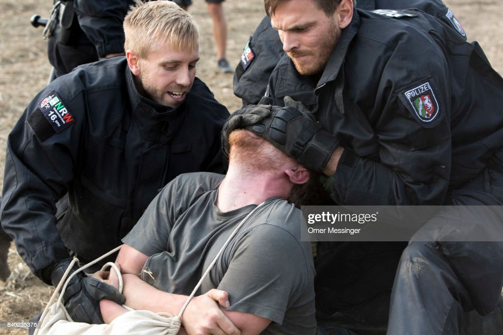 A protestor is detained by German police officers after he and others tried to reach a rail track in order to block it, in the Rhineland (Rhenisch) mines region west of Cologne on August 26, 2017 near the German village of Rath, Germany. The track serves as a main route for trains carrying coal to the power plants Thousands of protesters seeking to bring attention to the impact of coal on climate change have converged on the region for two days of disruptive disobedience. The mines, which include the Hambach, Garzweiler, Inden and Bergheim mines, are operated by German utility RWE and produce lignite coal.