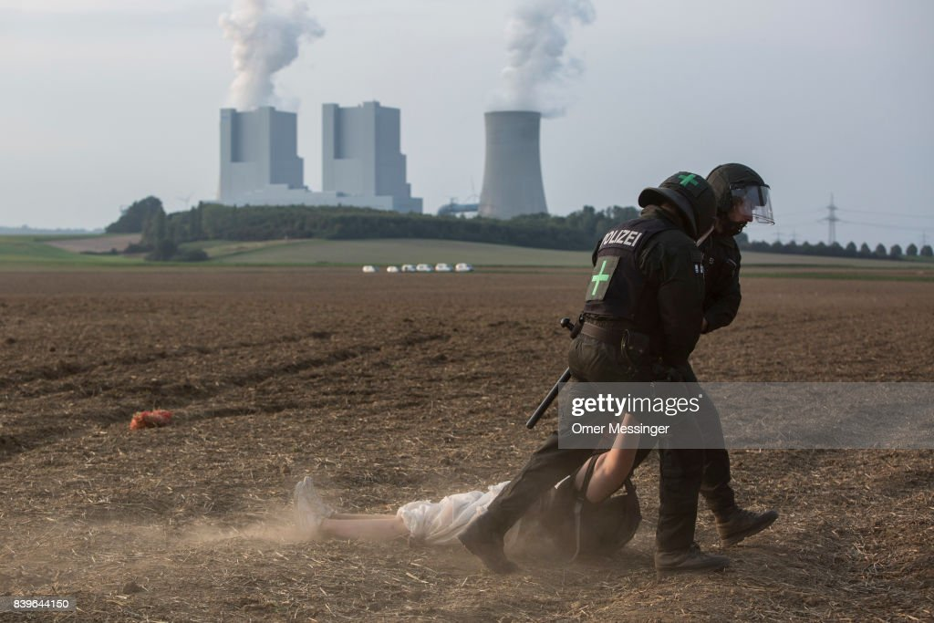 A protestor is detained by two German police officers after she and others tried to reach a rail track in order to block it, in the Rhineland (Rhenisch) mines region west of Cologne on August 26, 2017 near the German village of Rath, Germany. The track serves as a main route for trains carrying coal to the power plants Protesters seeking to bring attention to the impact of coal on climate change have converged on the region for two days of disruptive disobedience. The mines, which include the Hambach, Garzweiler, Inden and Bergheim mines, are operated by German utility RWE and produce lignite coal.