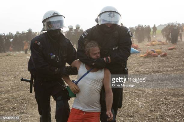 A protestor is detained by two German police officers after she and others tried to reach a rail track in order to block it in the Rhineland mines...