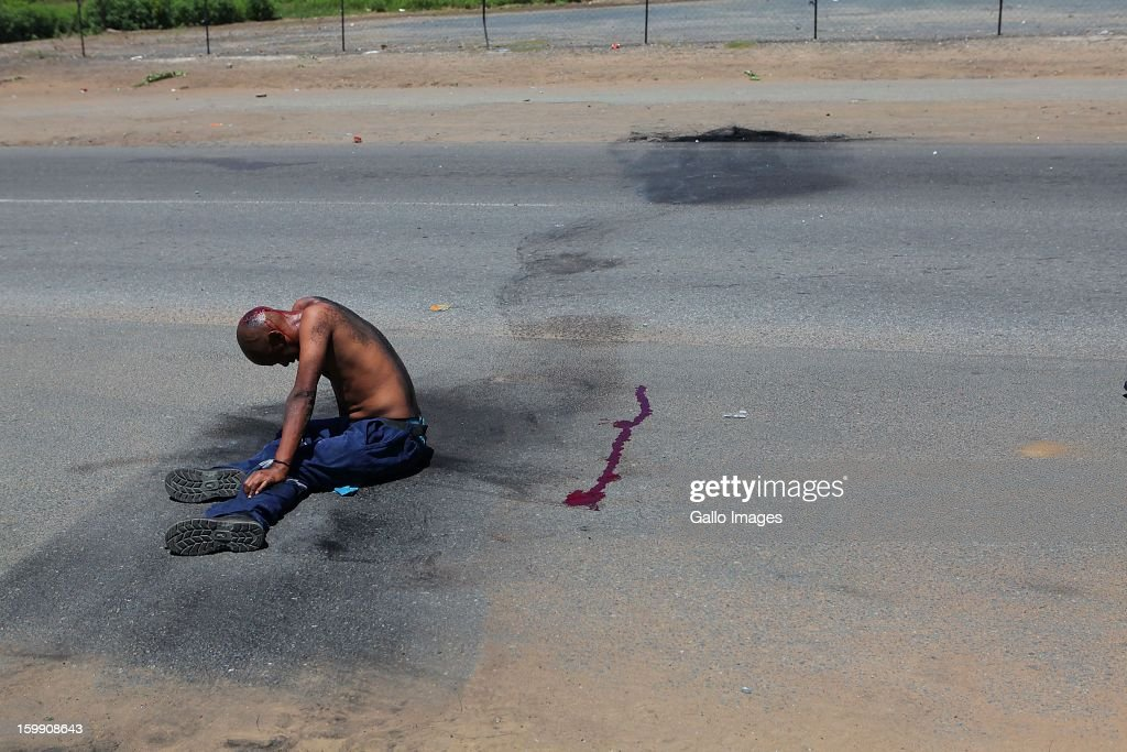 A protestor is knocked over by journalsit after throwing stones at their car on January 22, 2013, in Sasolburg, South Africa. The announcement of government's intention to merge municipalities in the Free State sparked outrage in Zamdela township residents.