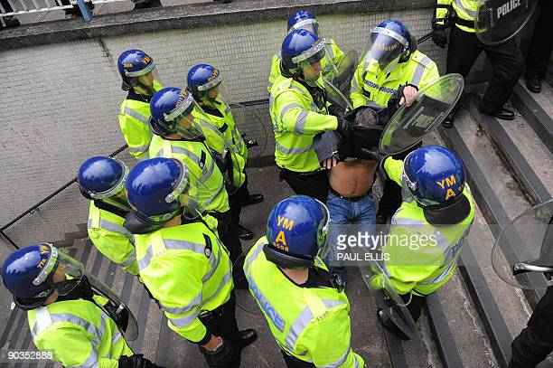A protestor is moved by police officers during a demonstration organised by the English Defence League after they clashed with antifascists...