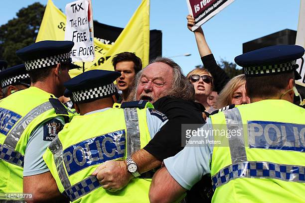 Protestor is pushed back by police as Prime Minister John Key delivers his post budget address at the Langham Hotel on May 25, 2012 in Auckland, New...