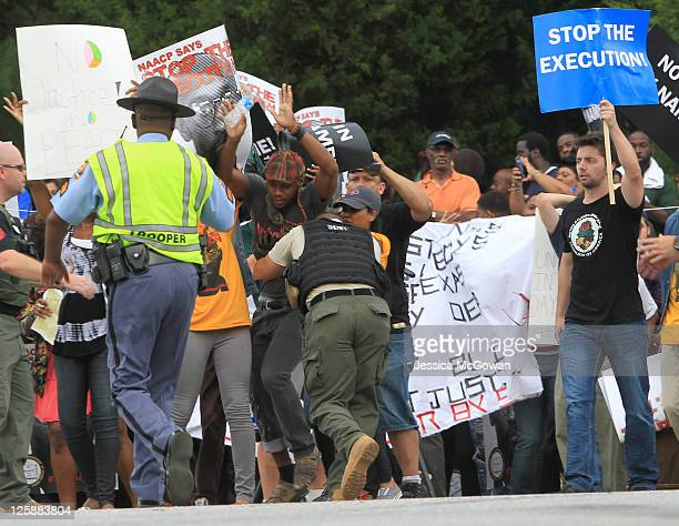 Protestor is subdue by law enforcement as he tries to cross the street to the Jackson State Prison where the planned execution of inmate Troy Davis...