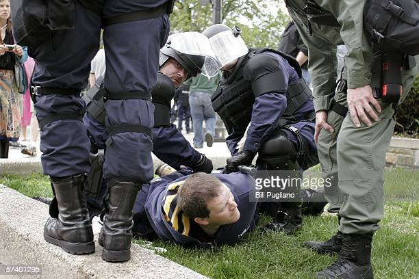 A protestor is subdued and arrested by police in riot gear during a Neonazi rally at the State Capital building April 22 2006 in Lansing Michigan...