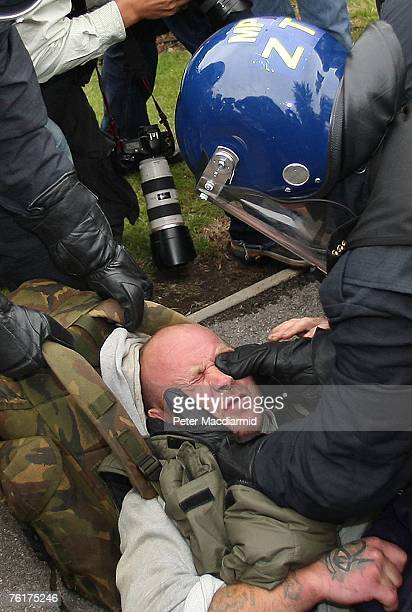 A protestor is subdued by riot police after a blockade of the British Airports Authority headquarters near Heathrow on August 19 2007 in London...