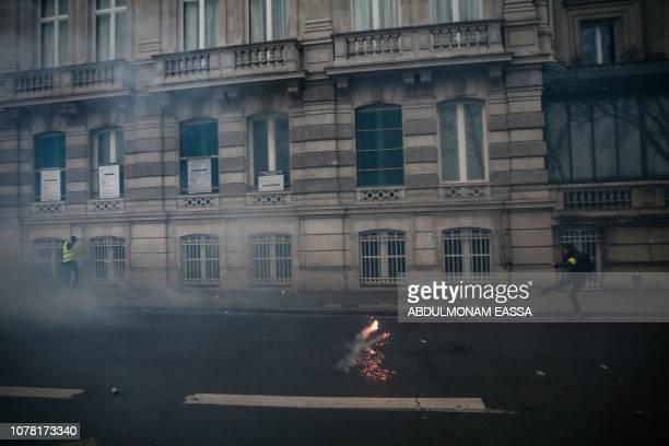 A protestor kicks a teargas shell in Paris on January 5 during an antigovernment demonstration called by the yellow vest 'Gilets Jaunes' movement...