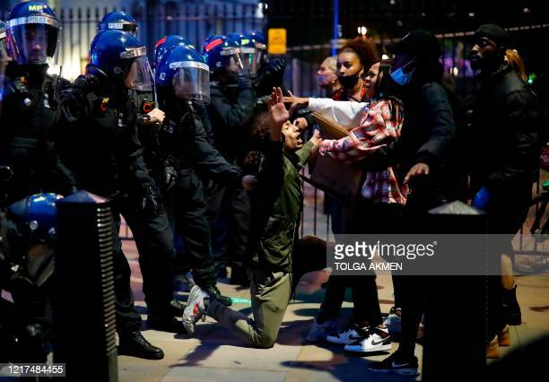 Protestor kneels in front of police officers in riot hemlets as he appeals for calm to his fellow protestors during an anti-racism demonstration in...