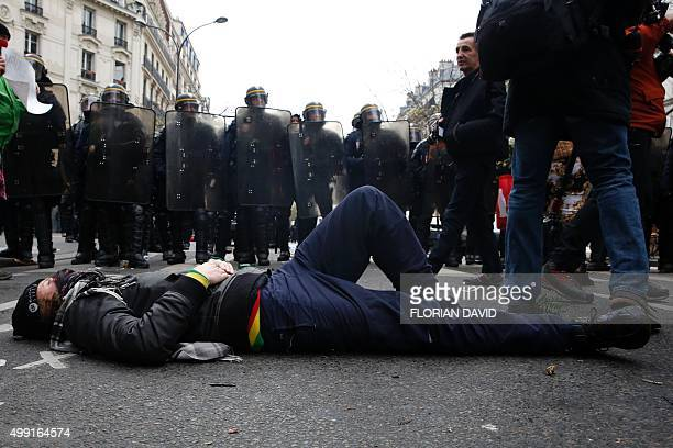 A protestor lies on the ground in front of riot police during a rally against global warming on November 29 2015 in Paris a day ahead of the start of...
