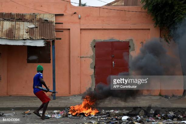 A protestor lights a bonfire during antigovernment demonstrations calling for constitutional reform on September 8 2017 in Lome The Togolese...