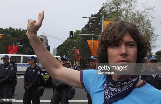A protestor makes a peace hand signal in front of police during a 'Stop Bush Make Howard History Rally' held at Sydney Town Hall September 8 2007 in...