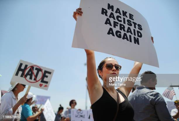 Protestor Michaela holds a sign reading 'Make Racists Afraid Again' at a protest against President Trump's visit following a mass shooting which left...