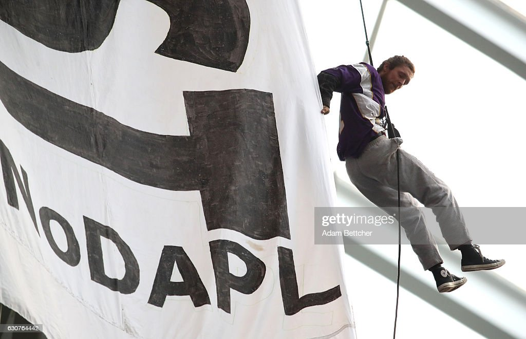 A protestor of the Dakota Access Pipeline hangs by a harness from the rafters during the second quarter of the Minnesota Vikings and Chicago Bears game on January 1, 2017 at US Bank Stadium in Minneapolis, Minnesota. Protestors unfurled a banner calling for the divestment of US Bank.