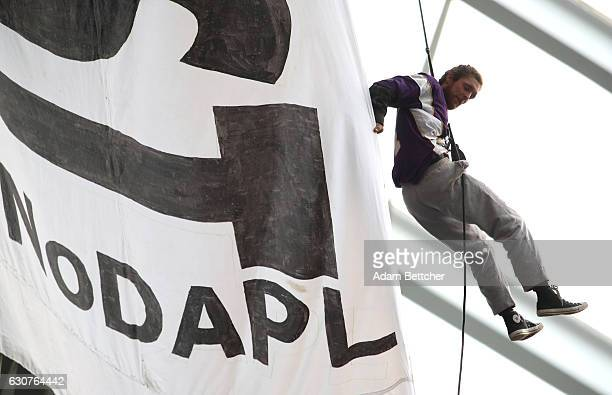 A protestor of the Dakota Access Pipeline hangs by a harness from the rafters during the second quarter of the Minnesota Vikings and Chicago Bears...